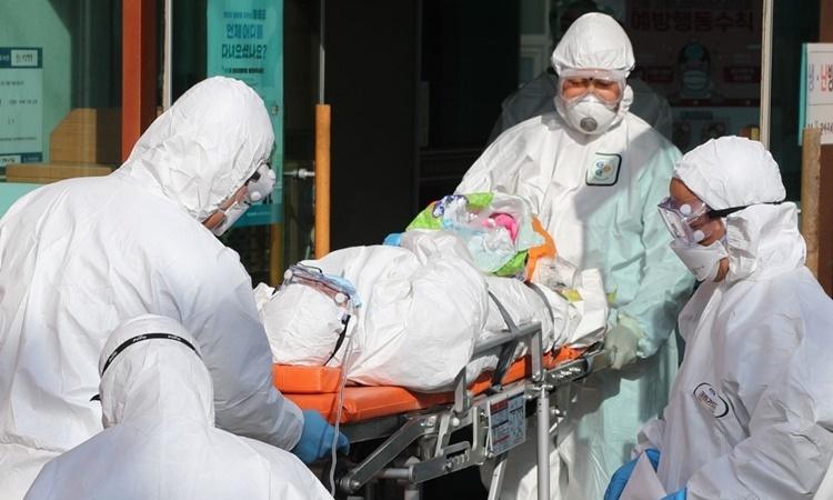 Nhân viên y tế di chuyển một bệnh nhân nghi nhiễm nCoV tại bệnh viện Daenam ở huyện Cheongdo, gần thành phố Daegu, ngày 21/2. Ảnh: AFP.