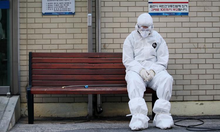 Nhân viên y tế nghỉ ngơi bên ngoài một bệnh viện ở Daegu hôm 23/2. Ảnh: AFP.