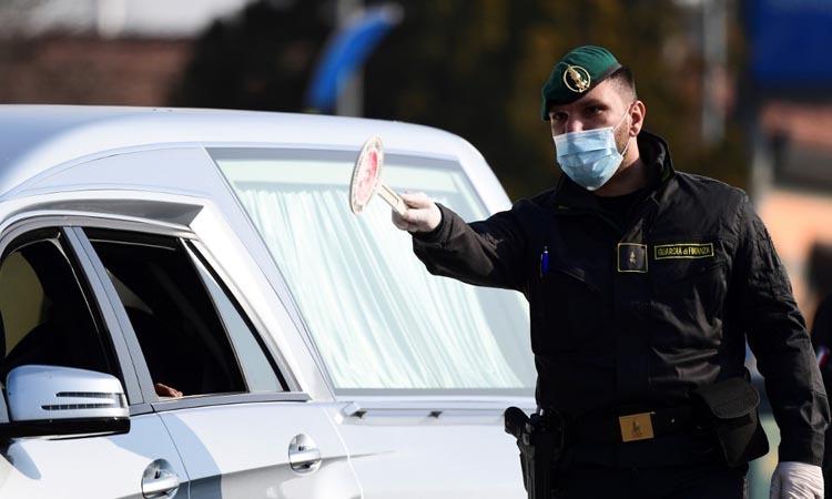 Nhân viên an ninh hướng dẫn giao thông tại một trạm kiểm soát ở thị trấn Zorlesco, vùng Lombardy, Italy hôm 24/2. Ảnh: AFP.
