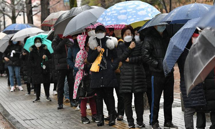 Người dân thành phố Daegu, Hàn Quốc xếp hàng trong mưa chờ mua khẩu trang y tế hôm nay. Ảnh: AFP.