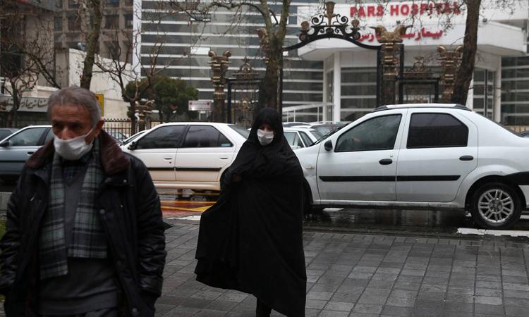 Hai người dânđeo khẩu trang bên ngoài bệnh viện ở thủ đô Tehran, Iran. Ảnh: NY Times.