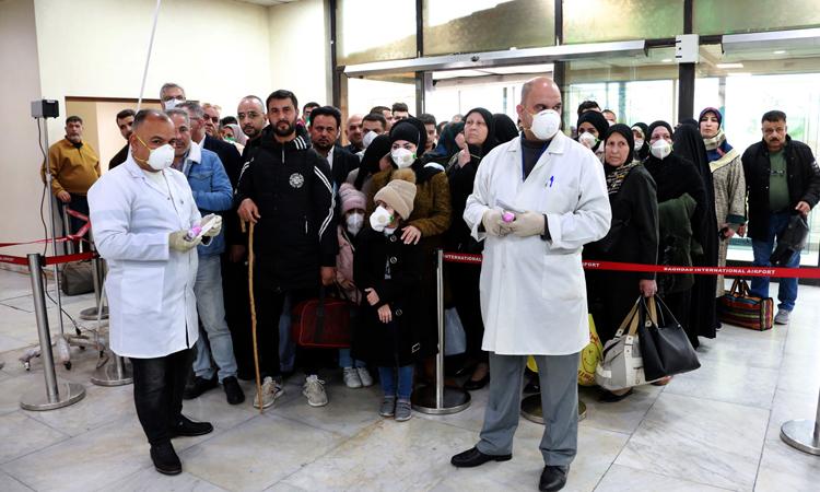 Nhân viên y tế đonhiệt độ cơ thể hành khách từ Iran tại sân bay ở Baghdad, Iraq. Ảnh: NY Times.