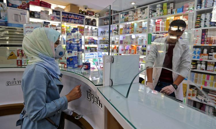 Người phụ nữ đeo khẩu trang tại hiệu thuốc ở thủ đô Tehran, Iran. Ảnh: AFP.