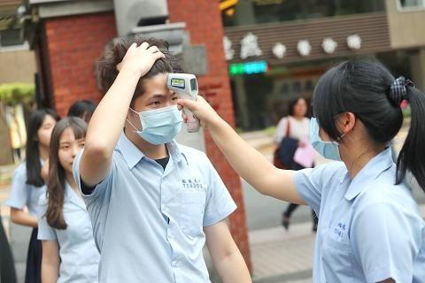 Học sinh trường trung học New Taipei Municipal Banciao tự kiểm tra thân nhiệt vào ngày 24/2. Ảnh: CNA.