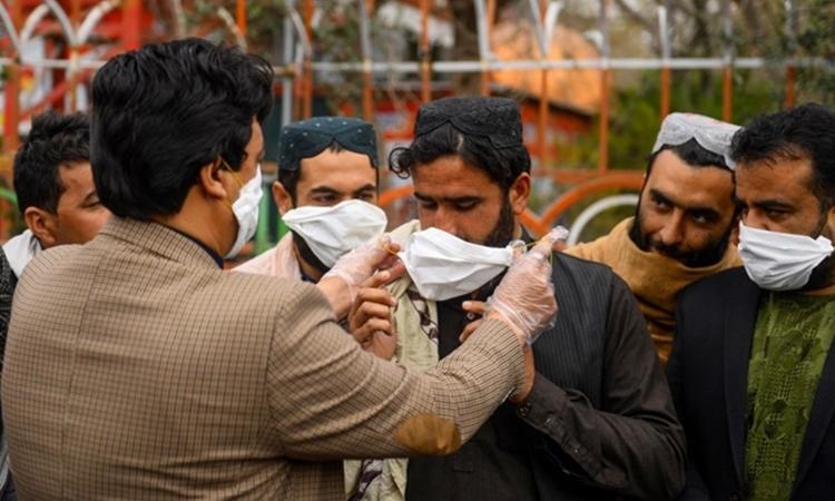 Tình nguyện viên Afghanistan phát khẩu trang tại Herat, nằm sát biên giới Iran ngày 26/2. Ảnh: AFP.