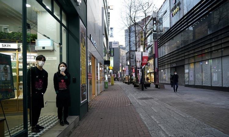 Các nhân viên một cửa hàng tại khu mua sắm Dongseong-ro, Daegu, Hàn Quốc đứng đợi khách hôm 21/2. Ảnh: Reuters.