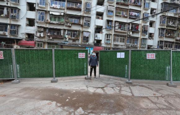 Một thanh niên đứng ở lối vào khu dân cư bị phong tỏa tại thành phố Nghi Xương, tỉnh Hồ Bắc, hôm 10/2. Ảnh: Reuters
