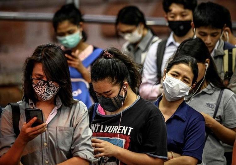 Người dân Thái Lan đeo khẩu trang, xếp hàng để lên thuyền qua sông Chao Phraya vào ngày 25/2. Ảnh: AFP
