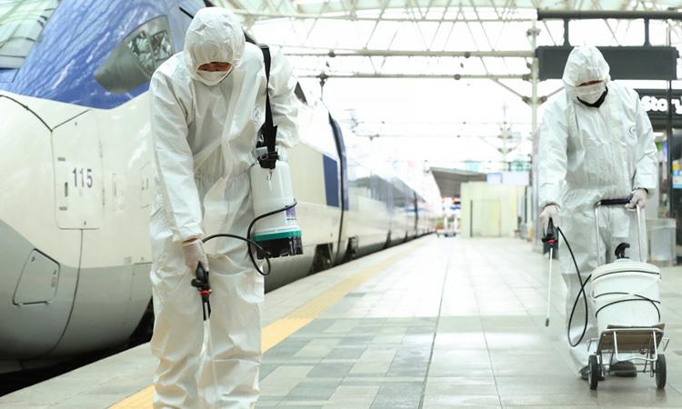 Nhân viên đường sắt Hàn Quốc phun thuốc khử trùng tại một ga tàu ở Seoul hôm 25/2. Ảnh: AFP.