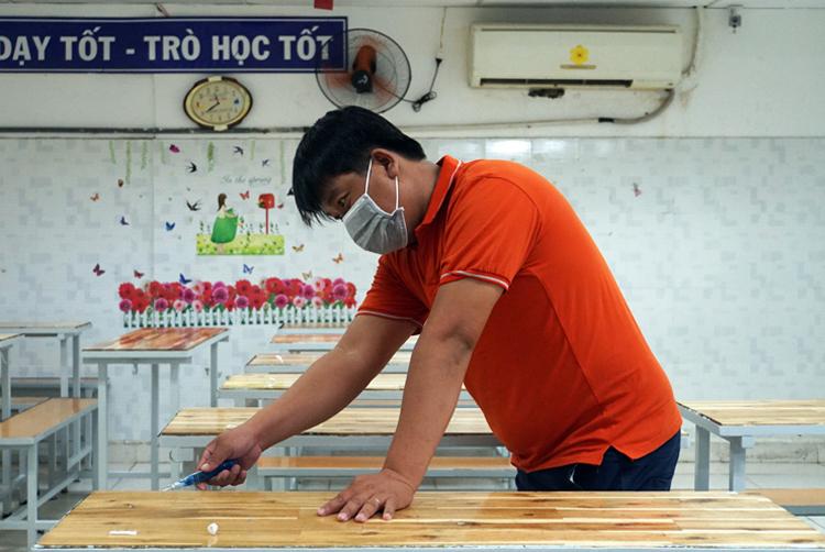 Giáo viên trường THCS - THPT Hồng Hà (TP HCM) vệ sinh, khử khuẩn lớp học ngày 22/4. Ảnh: Mạnh Tùng