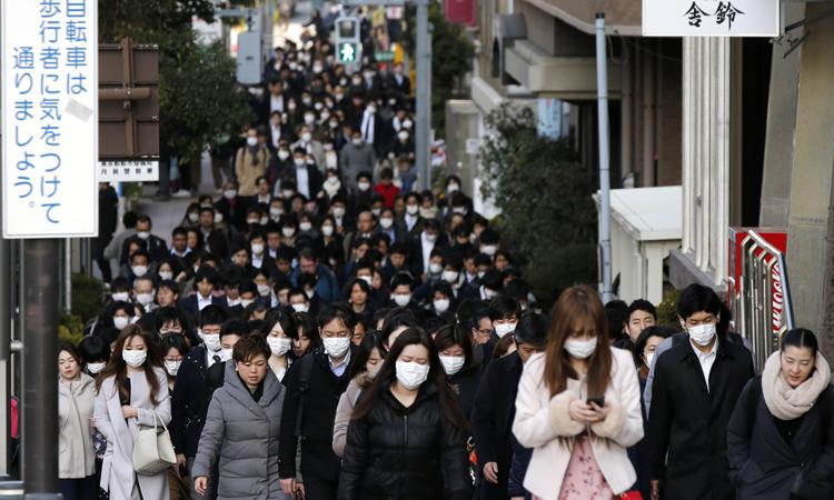 Dòng người đeo khẩu trang đi trên phố ởquận Chuo, Tokyo, Nhật Bản sáng 20/2. Ảnh: AP.