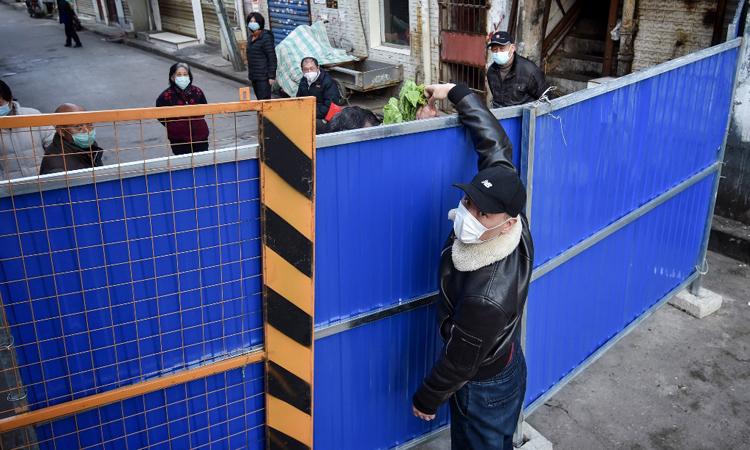 Một người đưa rau sang phía bên kia rào chắn tại thành phố Vũ Hán, tỉnh Hồ Bắc, Trung Quốc hôm 23/2. Ảnh: AFP.