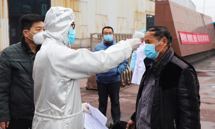 Người lao động nhập cư được kiểm tra thân nhiệt tại một nhà máy ở huyện Châu Bình, tỉnh Sơn Đông, Trung Quốc hôm 25/2. Ảnh: AFP.