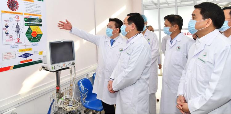 Bí thư Thành uỷ Hà Nội Vương Đình Huệ nghe lãnh đạo Bệnh viện đa khoa Đức Giang báo cáo công tác phòng, chống dịch. Ảnh: Viết Thành.