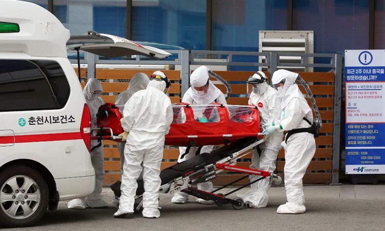 Nhân viên y tế di chuyển bệnh nhân nhiễm nCoV tại một bệnh viện ở thành phố Chuncheon, tỉnh Gangwon hôm 22/2. Ảnh: AFP.