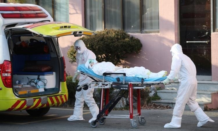 Các nhân viên y tế mặc đồ bảo hộ đưa một bệnh nhân nghi nhiễm nCoV vào một bệnh viện ở quận Cheongdo, gần thành phố Daegu, Hàn Quốc, hôm 21/2. Ảnh: AFP.