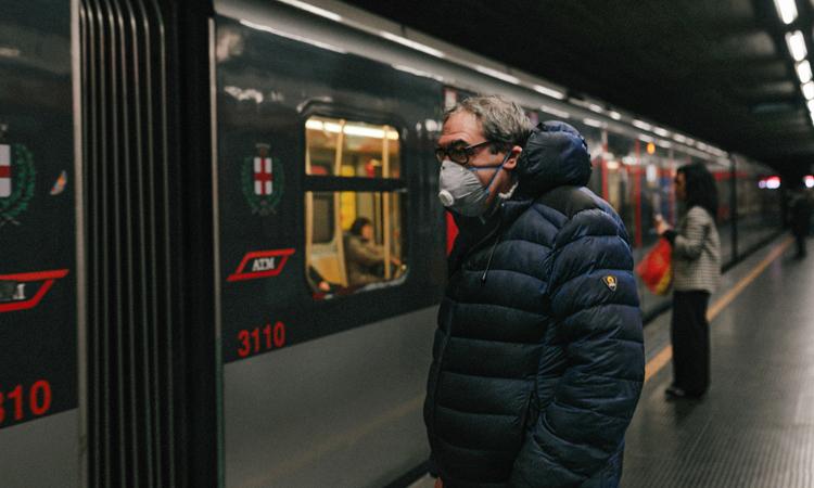 Hành khách đeo khẩu trang tại ga tàu điện ngầm ở Milan, Italy. Ảnh: NY Times.