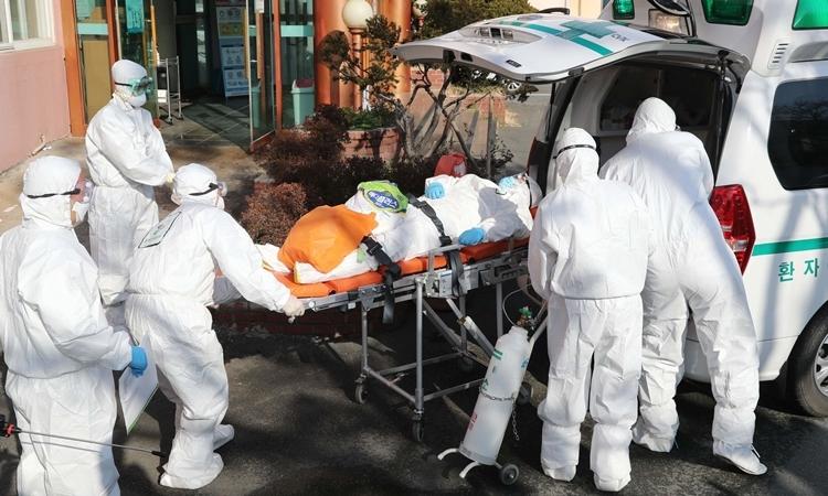 Nhân viên y tế đưa người nghi nhiễm nCoV vào bệnh viện ở Hàn Quốc ngày 21/2. Ảnh: AFP.