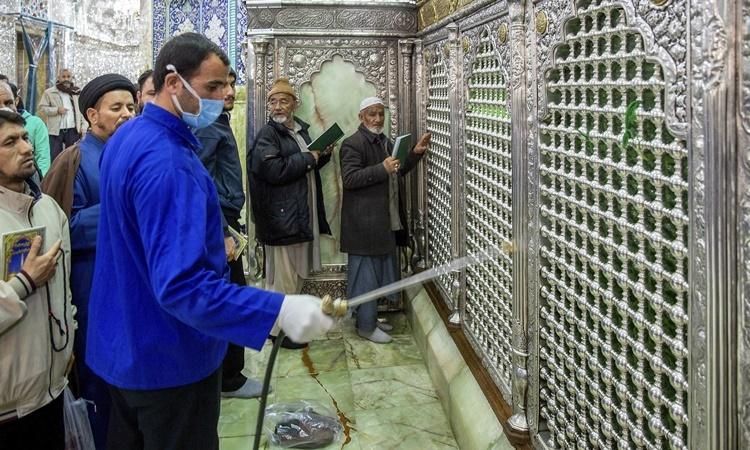 Người đàn ông phun thuốc tẩy trùng một đền thờ ở thành phố Qom, Iran, ngày 24/2. Ảnh: AP.