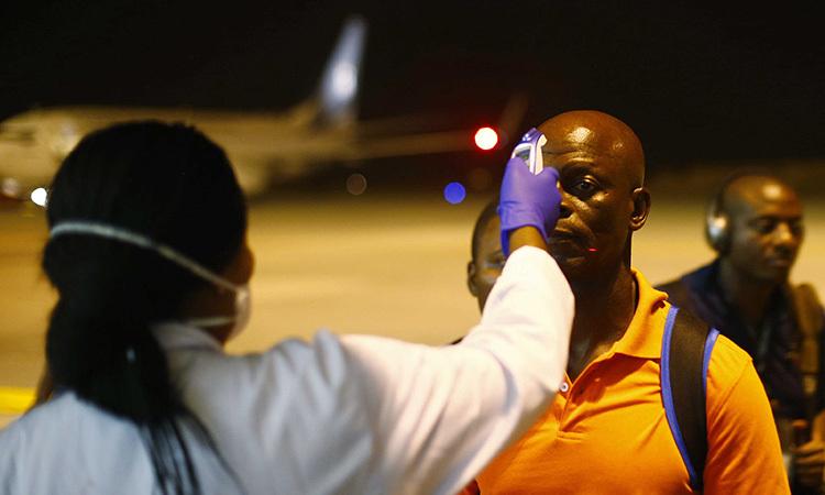 Nhân viên y tế đo thân nhiệt hành khách tại sân bay quốc tế Bata, Guinea Xích đạo hôm 14/1. Ảnh: Reuters.
