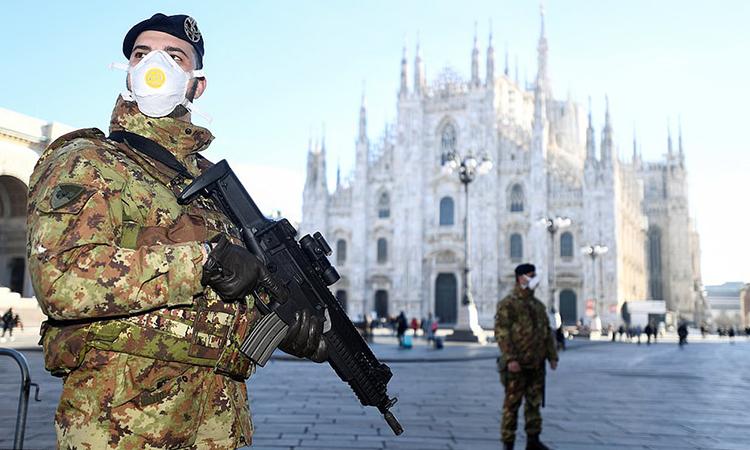 [Quân nhân Italy đeo khẩu trang, tuần trabên ngoài nhà thờ lớn Duomo ở Milan hôm 24/2. Ảnh: Reuters.