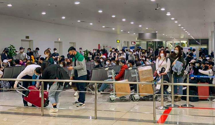 Số hành khách từ Hàn Quốc về Việt Nam tối 27/2 ngồi chờ tại tầng 2 để kiểm soát y tế. Ảnh: Giang Kim Bùi