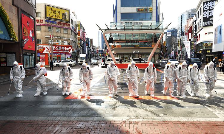 Binh lính Hàn Quốcmặc đồ bảo hộ phun thuốc khử trùng ở thành phố Daegu, hôm 27/2. Ảnh: AP.