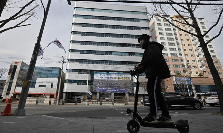 Một người đeo khẩu trang lái scooter trên phố đối diện tòa nhà của Tân Thiên Địa ở thành phố Daigu. Ảnh: AFP.