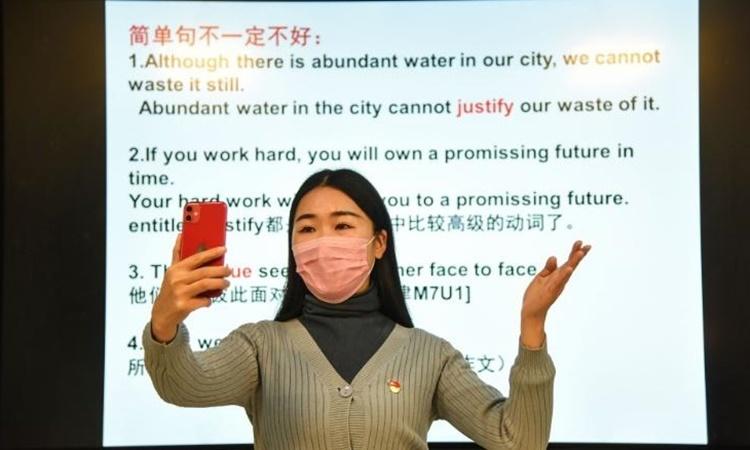 Một giáo viên giảng bài qua điện thoại di động ở thành phố Đông Hải, tỉnh Giang Tô, Trung Quốc, ngày 17/2. Ảnh: AFP.