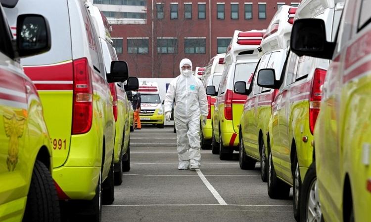 Một nhân viên y tế mặc đồ bảo hộ đi giữa những xe cứu thương ở thành phố Daegu hôm nay. Ảnh: AFP.