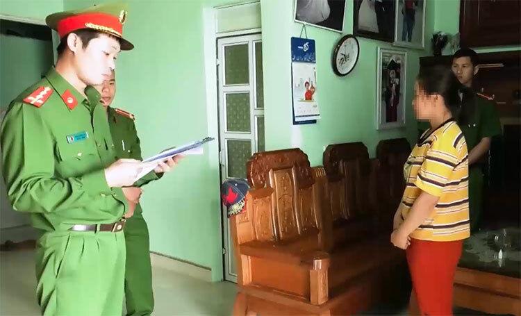 Vợ Thông (áo vàng) nghe cảnh sát đọc lệnh khởi tố chồng. Ảnh: C.A