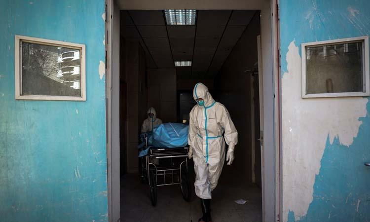 Nhân viên y tế mặc đồ bảo hộ vận chuyển thi thể người chết vì nCoV tại bệnh viện ở Vũ Hán, tỉnh Hồ Bắc. Ảnh: AP.