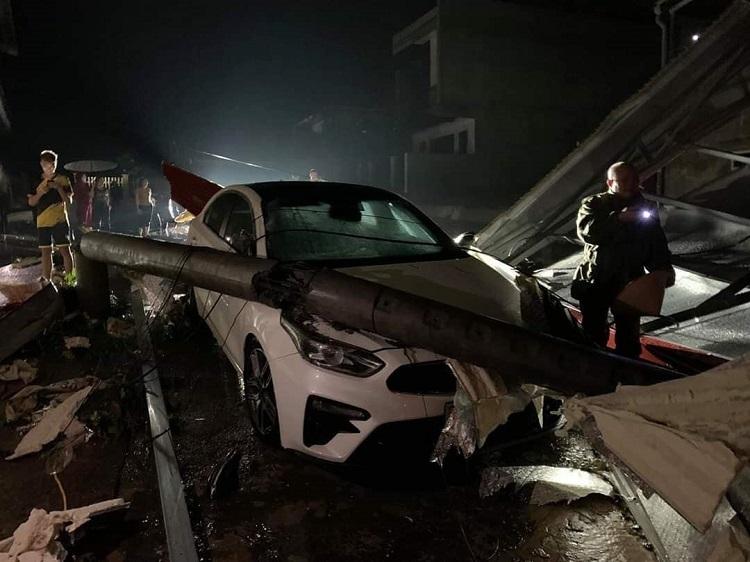 Cột điện đổ lên ôtô ở thành phố Yên Bái. Ảnh: TH Yên Bái