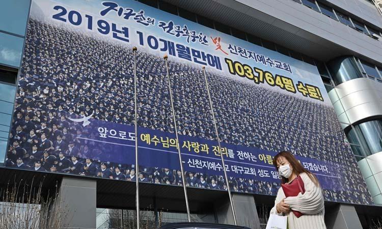Người phụ nữ đeo khẩu trang trước cửa trụ sở chi nhánh Tân Thiên Địa ở thành phố Daegu hôm 27/2. Ảnh: AFP.