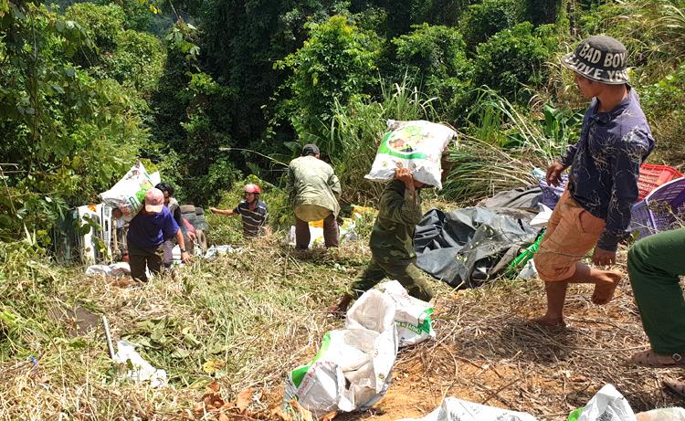 Người dân vác hàng trăm bao phân bón lên đường giúp tài xế. Ảnh: Hoài Thanh.