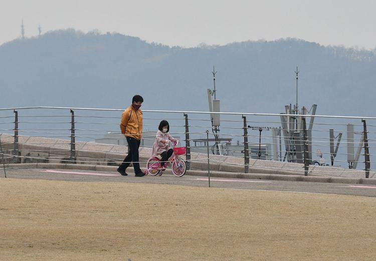 Một ông bố đưa con đi đạp xe ở công viên tại thành phố Daegu hôm 28/2. Ảnh: AFP