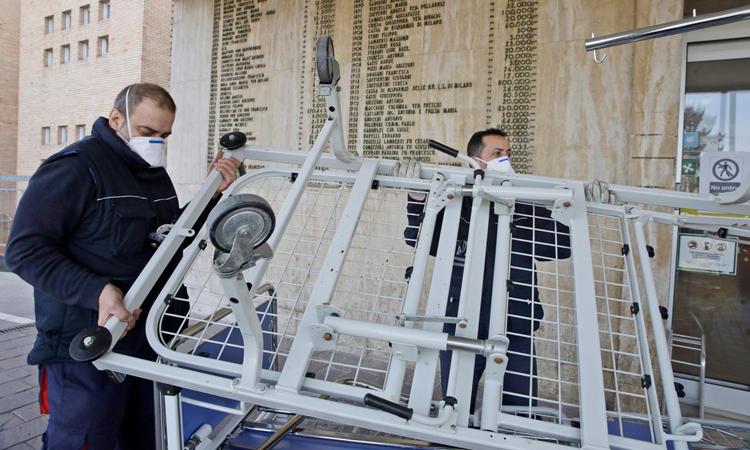 Hai nhân viên vận chuyển giường bệnh mới tới bệnh viện thành phố  Codogno,vùng Lombardy. Ảnh: AP.
