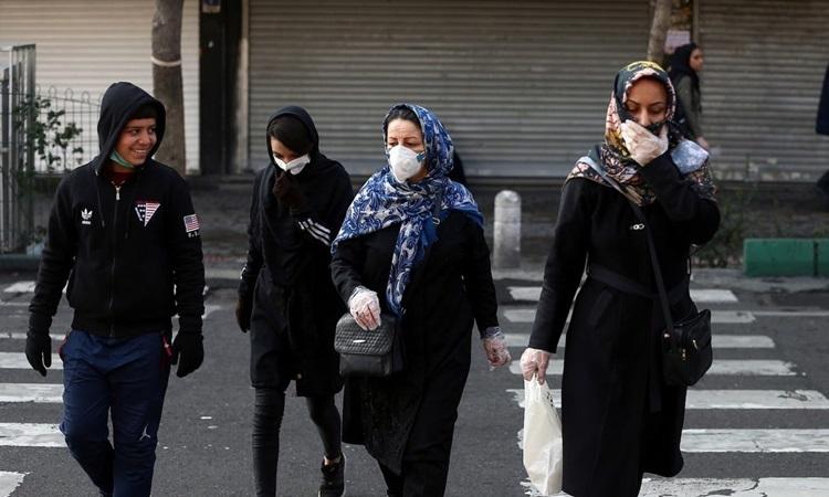 Người dân ở thủ đô Tehran của Iran đeo khẩu trang khi đi trên đường hôm 29/2. Ảnh: Reuters.
