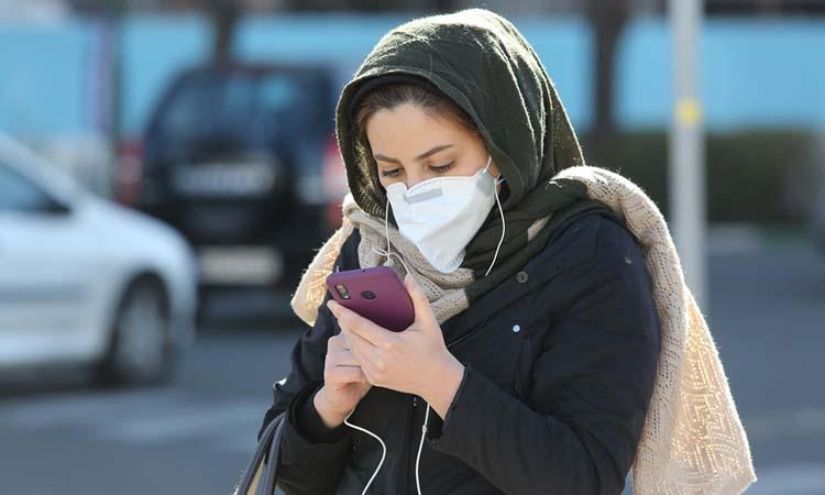Người phụ nữ đeo khẩu trang đang xem điện thoại ở thủ đô Tehran. Ảnh: AFP.
