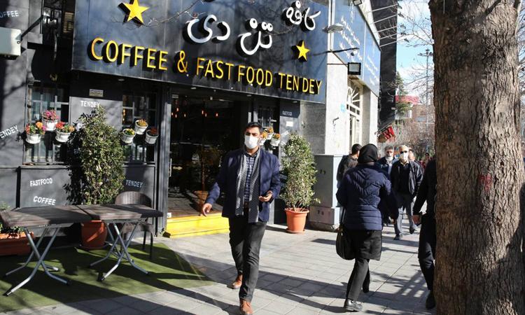 Người đàn ông đeo khẩu trang đi bên ngoài một cửa hàng đồ ăn nhanh ở thủ đô Tehran. Ảnh: AFP.