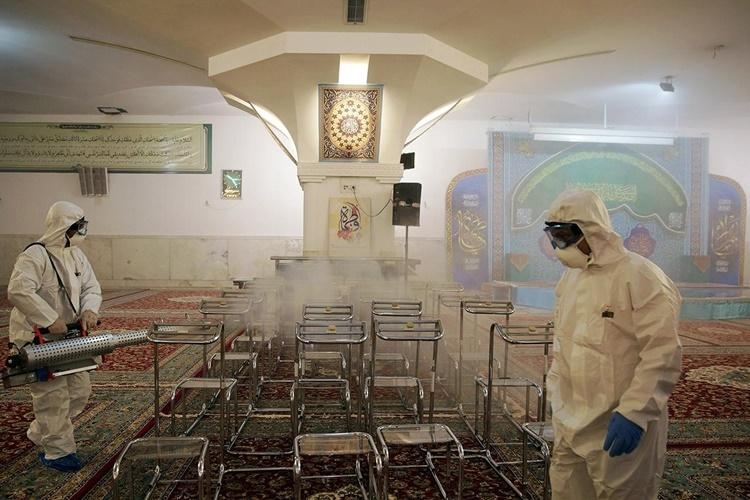 Nhân viên y tế tẩy trùng một nhà thờ Hồi giáo ở Mashhad, Iran, ngày 27/2. Ảnh: Reuters.