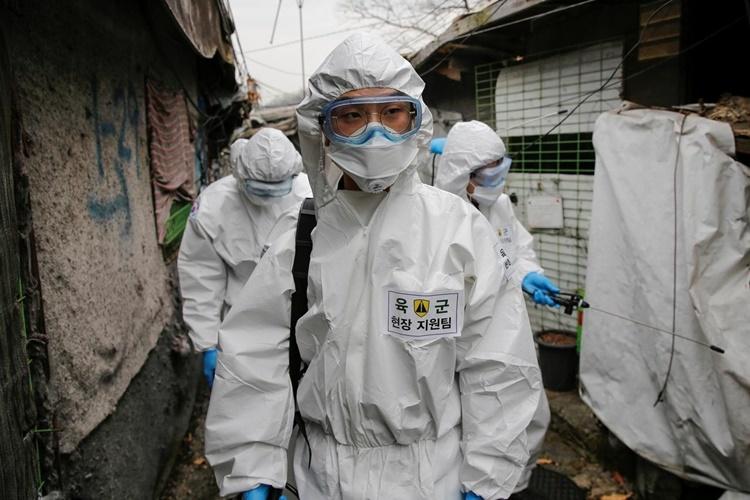 Binh sĩ Hàn Quốc mặc đồ bảo hộ thực hiện công tác tẩy trùng tại làng Guryong ở Seoul, Hàn Quốc, ngày 3/3. Ảnh: Reuters.
