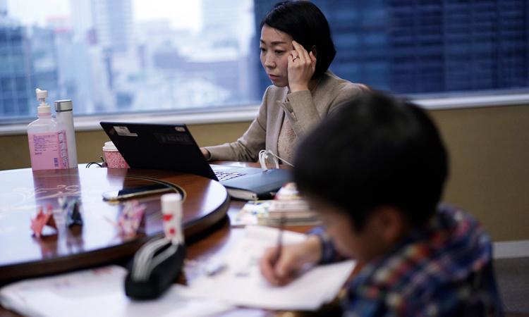 Một phụ huynh làm việc trong lúc con của cô làm bài tập tại Tokyo, Nhật Bản hôm 2/3. Ảnh: AP.
