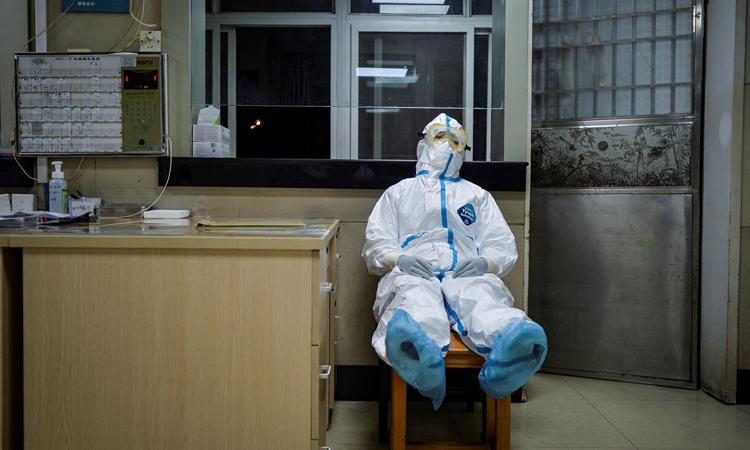 Nữ nhân viên y tế tranh thủ chợp mắt giữa ca trực đêm tại trung tâm y tế cộng đồng ở Vũ Hán, tỉnh Hồ Bắc hôm 9/2. Ảnh: Reuters.