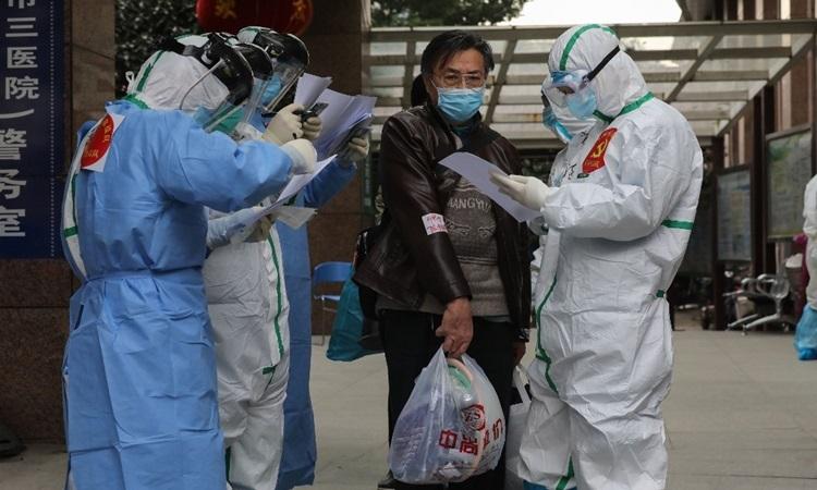 Nhân viên y tế Vũ Hánkiểm tra thông tin khi bệnh nhân nhiễm nCoVrời Bệnh viện số 3đến Bệnh viện Hỏa Thần Sơn hôm 4/3. Ảnh: AFP.