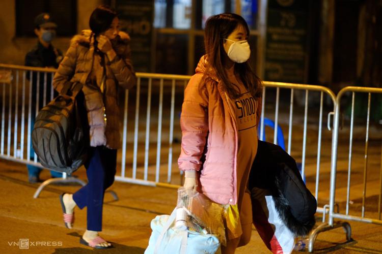 Một số người mang đồ đạc đi ra khỏi khu vực bị chốt chặn ở phố Trúc Bạch. Ảnh: Giang Huy