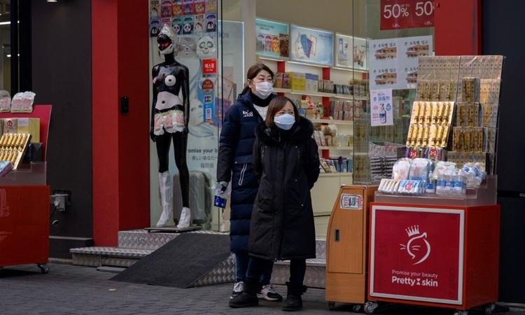 Nhân viên bán hàng đeo khẩu trang đứng bên ngoài cửa hiệu mỹ phẩm ở thủ đô Seoul của Hàn Quốc hôm nay. Ảnh: AFP.