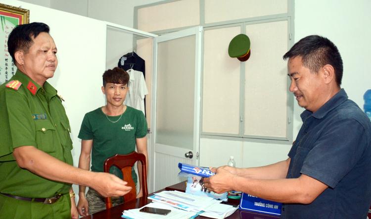 Anh Hoàng Nam (giữa) chứng kiến công an trao trả số tiền mình nhặt được cho ông Quý. Ảnh: Lan Vy.