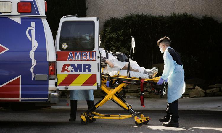 Nhân viên y tế chuyển bệnh nhân nhiễm nCoV lên xe cứu thương ở Life Care Center hôm 4/3. Ảnh: Reuters.