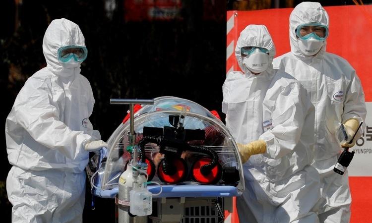 Nhân viên y tế di chuyển một người nghi nhiễm nCoV tại Bệnh viện Đại học Quốc gia Kyungpook ở Daegu ngày 6/.3 Ảnh: Reuters.